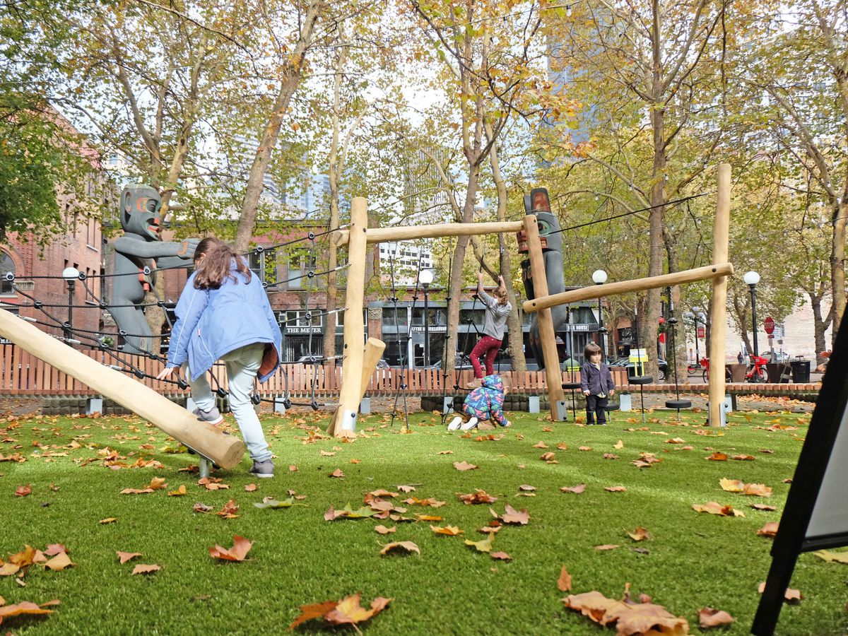 On a grassy field, a playground is made out of logs, including a climbing structure to the left and some swings ahead.