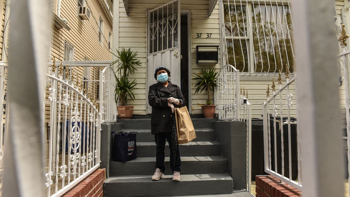 A woman with a face mask and a bag stands on the stairs of a house door.