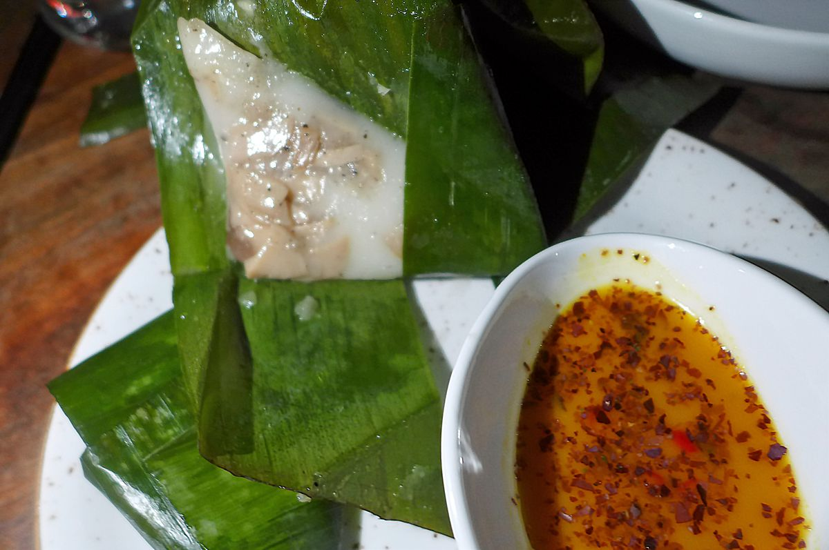 Little white swatches wrapped in banana leaves with an orange dipping sauce on the side.