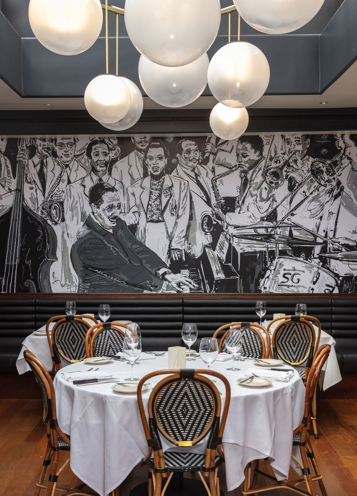 A black and white jazz mural inside an upscale restaurant with white tablecloths.