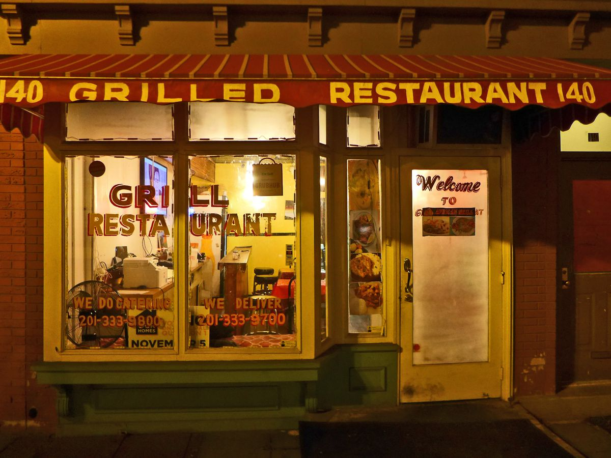 An antique storefront at night, glowing, with Grill Restaurant stenciled on the window.