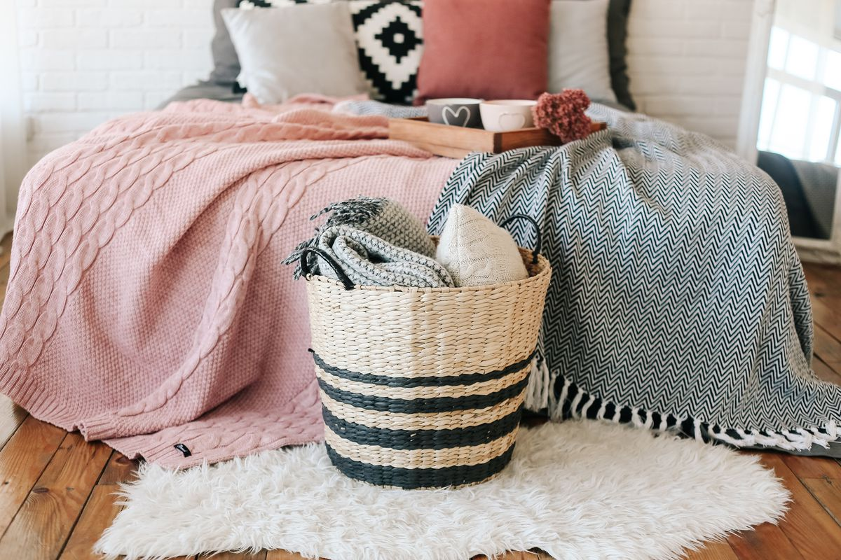 Bedroom interior with a rustic bed with blankets in a basket on the floor.