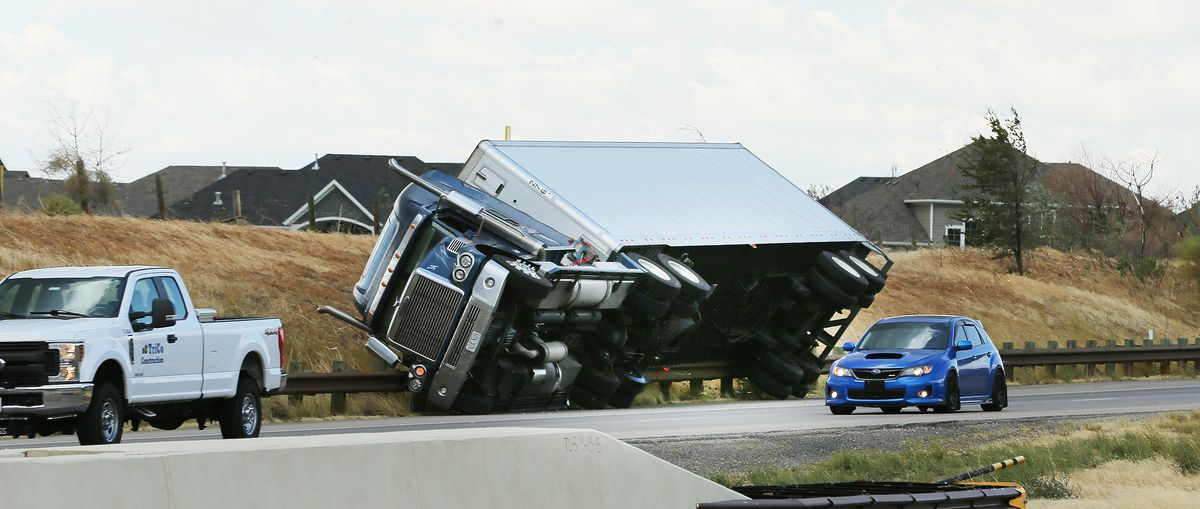 A semitractor-trailer rests on a guardrail after being blown over by high winds on Legacy Highway between Centerville and Farmington on Tuesday, Sept. 8, 2020.