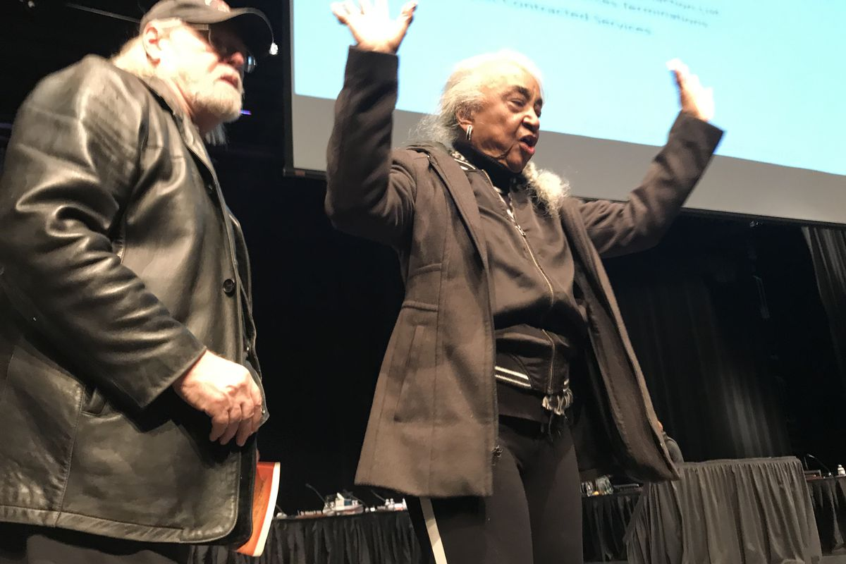 Detroit activist Helen Moore speaks with her supporters from the stage at Mumford High School. Her removal from the auditorium prompted loud objections that led to the meeting's abrupt ending.