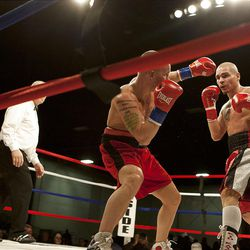 """Chris """"KidKayo"""" Fernandez, right, eyes his opponent Allen Litzau during their boxing match at the South Towne Expo Center. Fernandez won the bout after four rounds, Saturday, Dec. 15, 2012."""