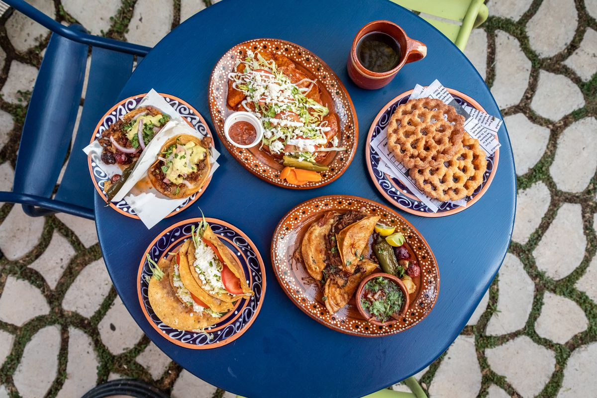 Array of dishes from Barra de Pan, a licensed home restaurant in Riverside, California on a blue cafe table and ornate tiled garden flooring.