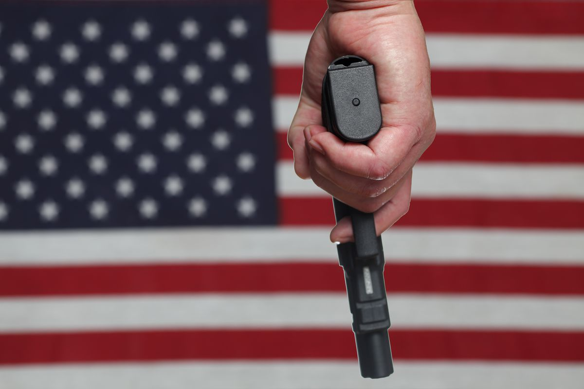 A man holding a handgun in front of the US flag.