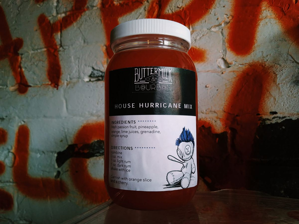 A jar of liquid has a label with a recipe for making a hurricane cocktail. It's in front of a white wall with red graffiti.