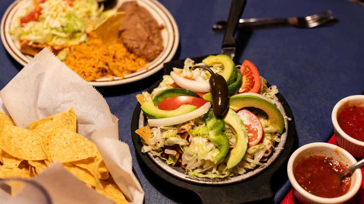 A platter of botana with sliced avocado, tomato, and green bell pepper arranged on top