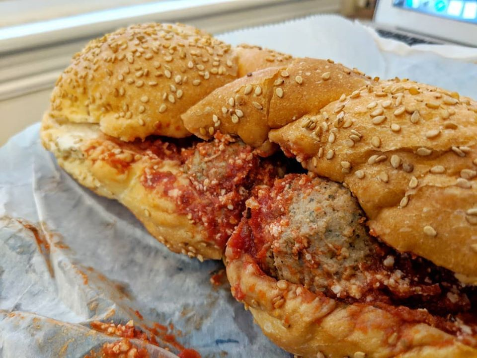 A meatball sub sits on white deli paper