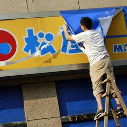 A worker covers a signboard of a Japanese restaurant chain with blue sheets ahead of major protests expected on Tuesday, near the Japanese Consulate General Monday Sept. 17, 2012 in Shanghai, China. China moved to tamp down rising anti-Japan sentiment after a weekend of sometimes violent demonstrations, threatening Monday to arrest lawbreakers and scrubbing websites of protest-related images and posts.