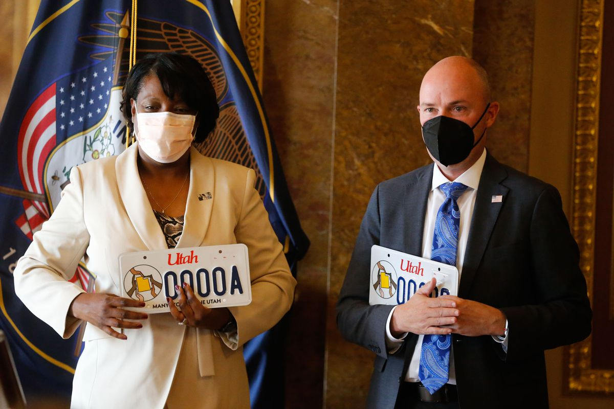 Rep. Sandra Hollins, D-Salt Lake City, left, and Gov. Spencer Cox participate in the launch of new Utah license plate.