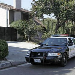 """A Los Angeles County Serriff's deputy in a patrol car passes the home of Nakoula Basseley Nakoula, the man who made the film """"Innocence of Muslims"""" that has sparked violent protests, on a street in Cerritos, Calif., Tuesday, Sept. 25, 2012. The filmmaker has received death threats and was forced into hiding, putting his house up for sale, after the 14-minute movie trailer rose to prominence."""