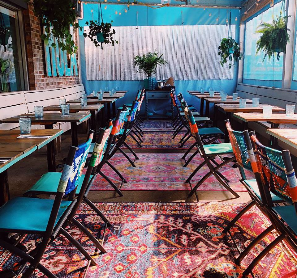 A tented patio with pattered rugs on the floor and Hola's signature turquoise colored chairs at the tables
