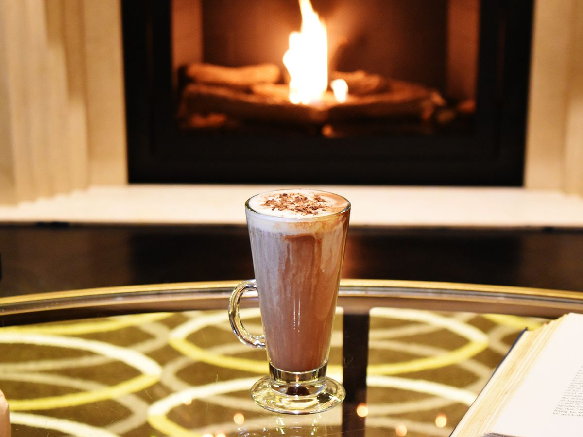 a hot chocolate in a glass in front of a fire