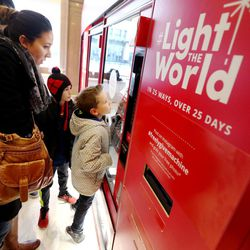 Brittany Ryan helps her son Hudson at the Light the World charity vending machines in the Joseph Smith Memorial Building in Salt Lake City on Friday, Dec. 15, 2017.