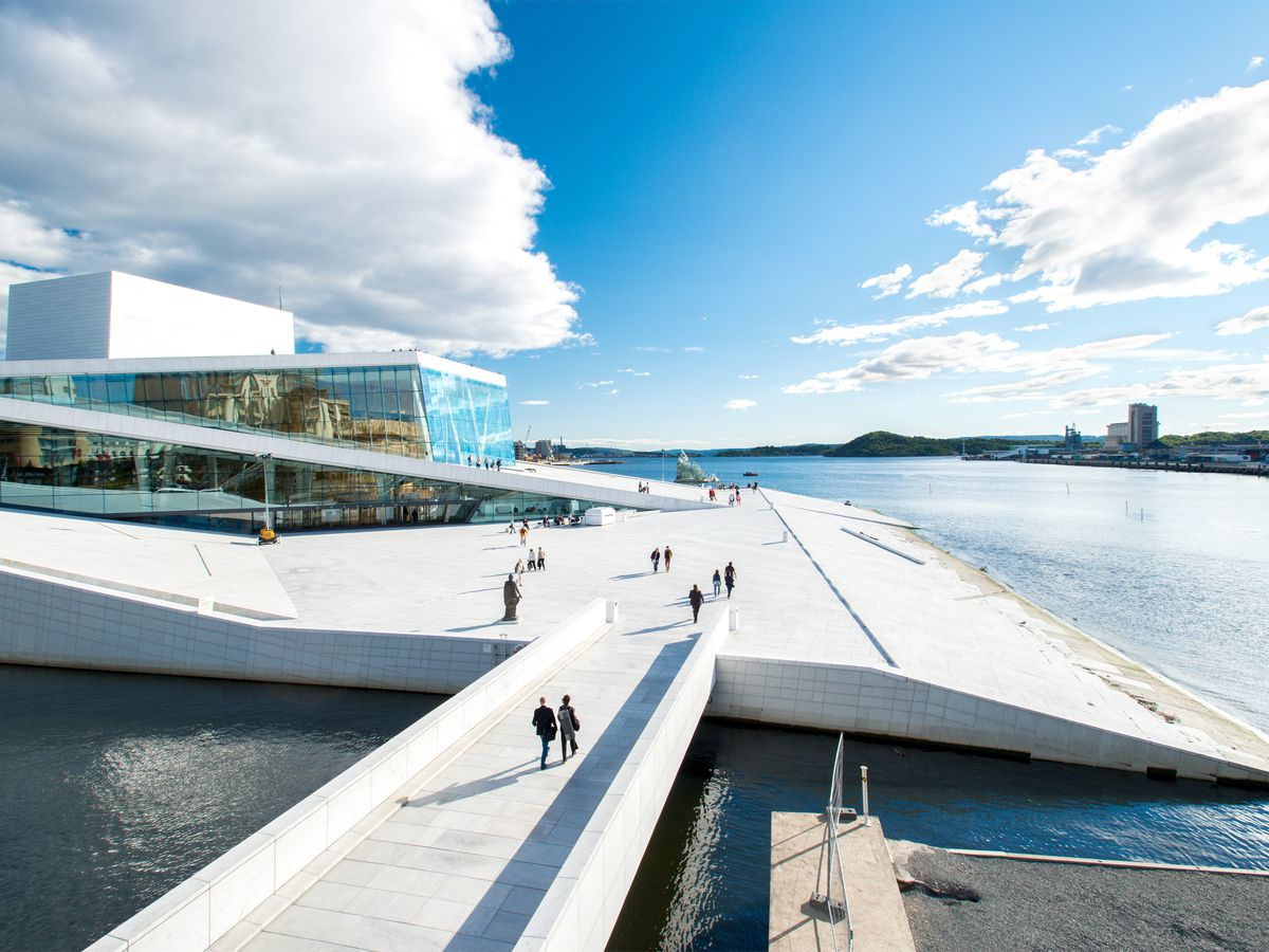 A white bridge carries people across the water to a striking angled building. The white granite-and-marble form slopes gently upwards, and visitors can climb to the roof for harbor views.