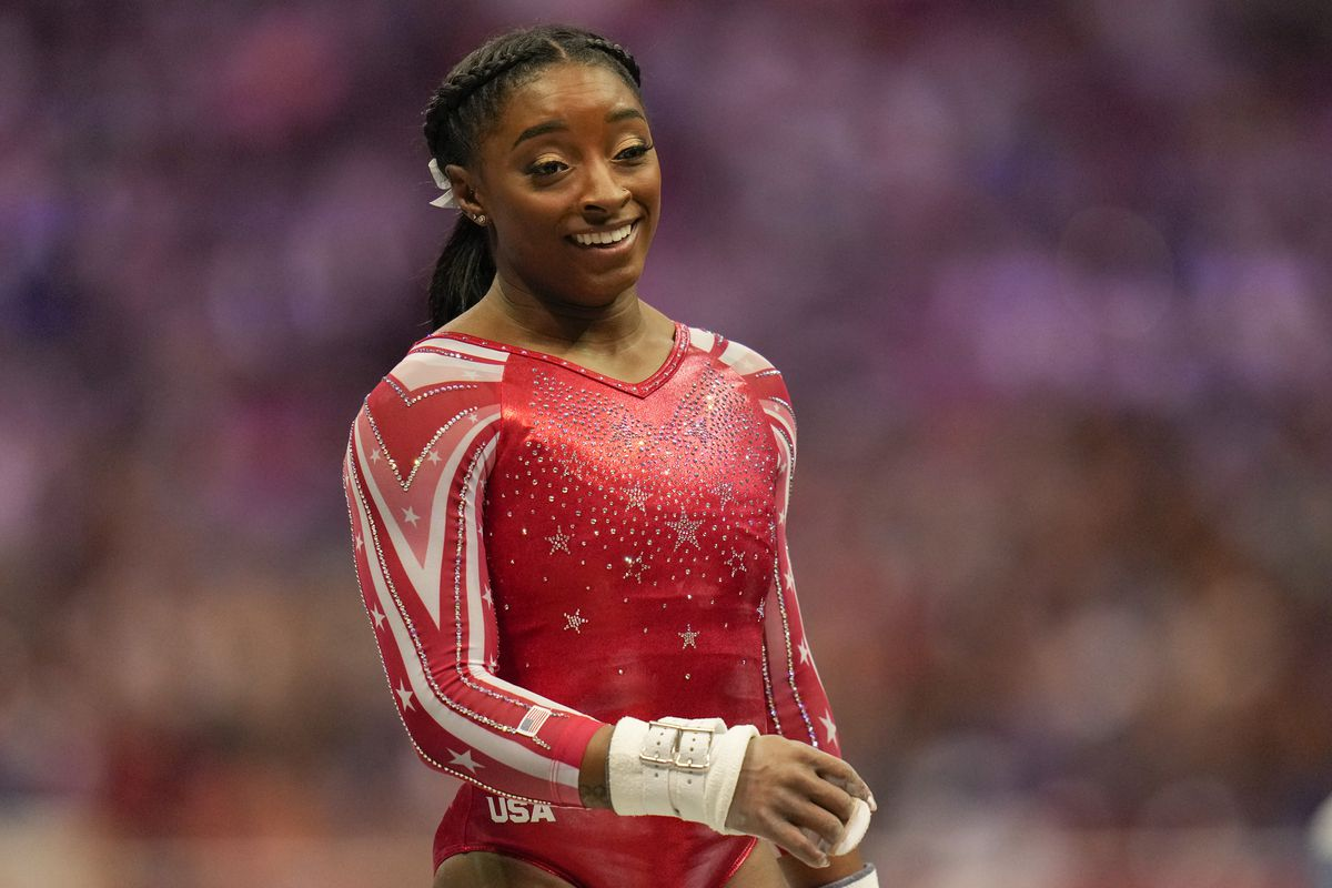 Simone Biles smiles after competing on the uneven bars during the women's U.S. Olympic Gymnastics Trials on Sunday.