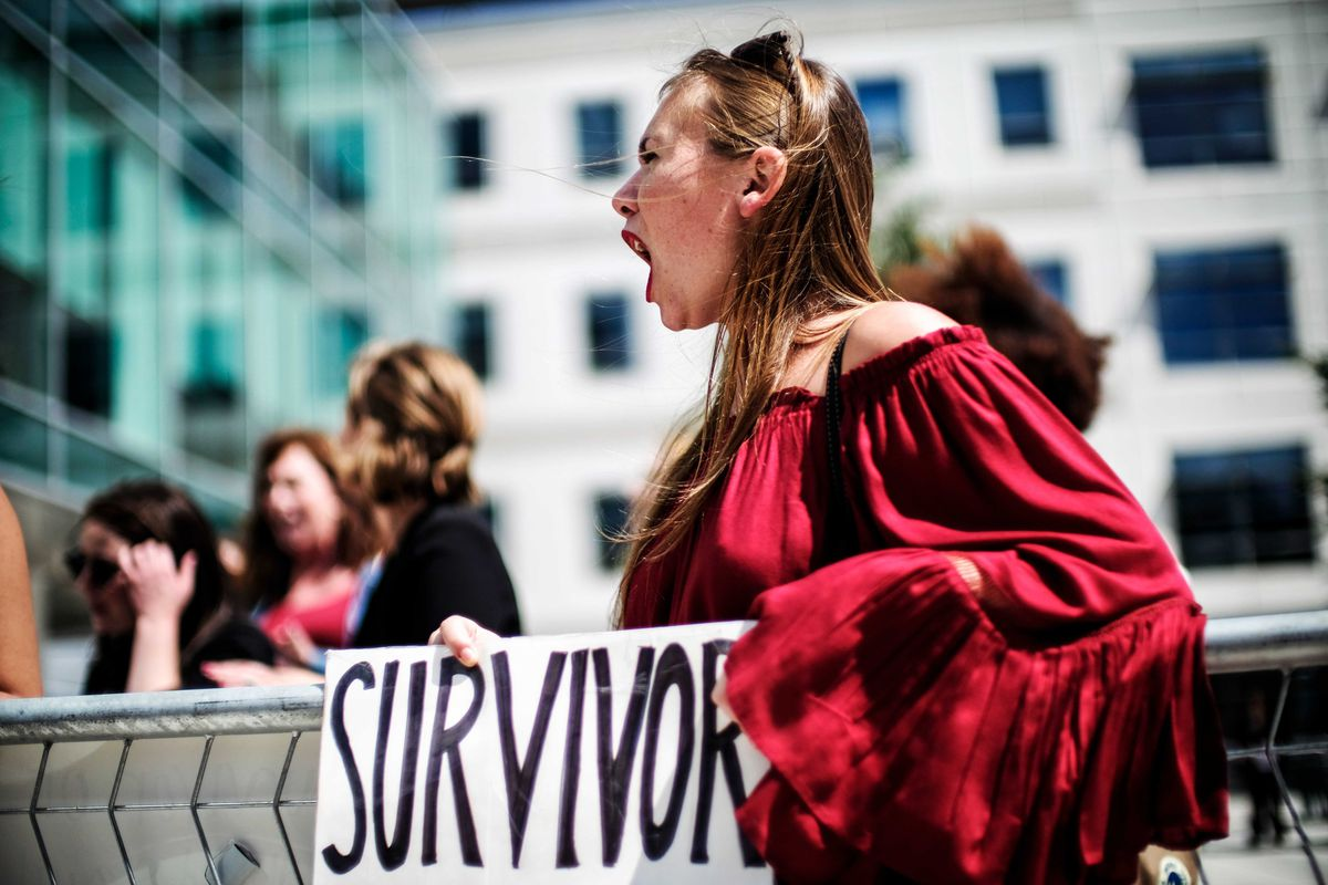 """A woman in a red shirt holds a sign reading """"Survivor"""" during a protest."""