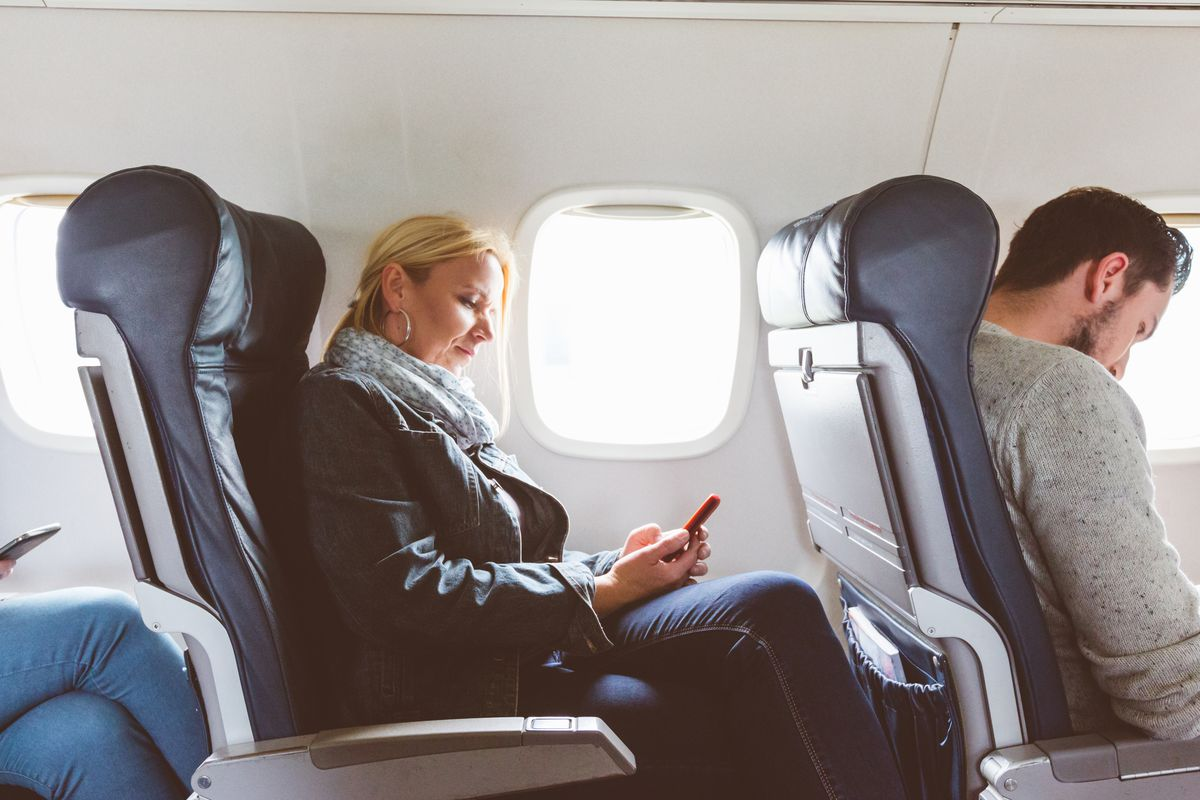 Woman sitting on an airplane using her phone during a flight. A man sits in the seat in front of her.