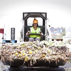 """A worker at an EcoScraps location hauls produce brought in to be made into compost and other garden boosters. EcoScraps was helped by an economic self-reliance program at BYU, which was honored as a """"Changemaker Campus"""" Monday by Ashoka U."""