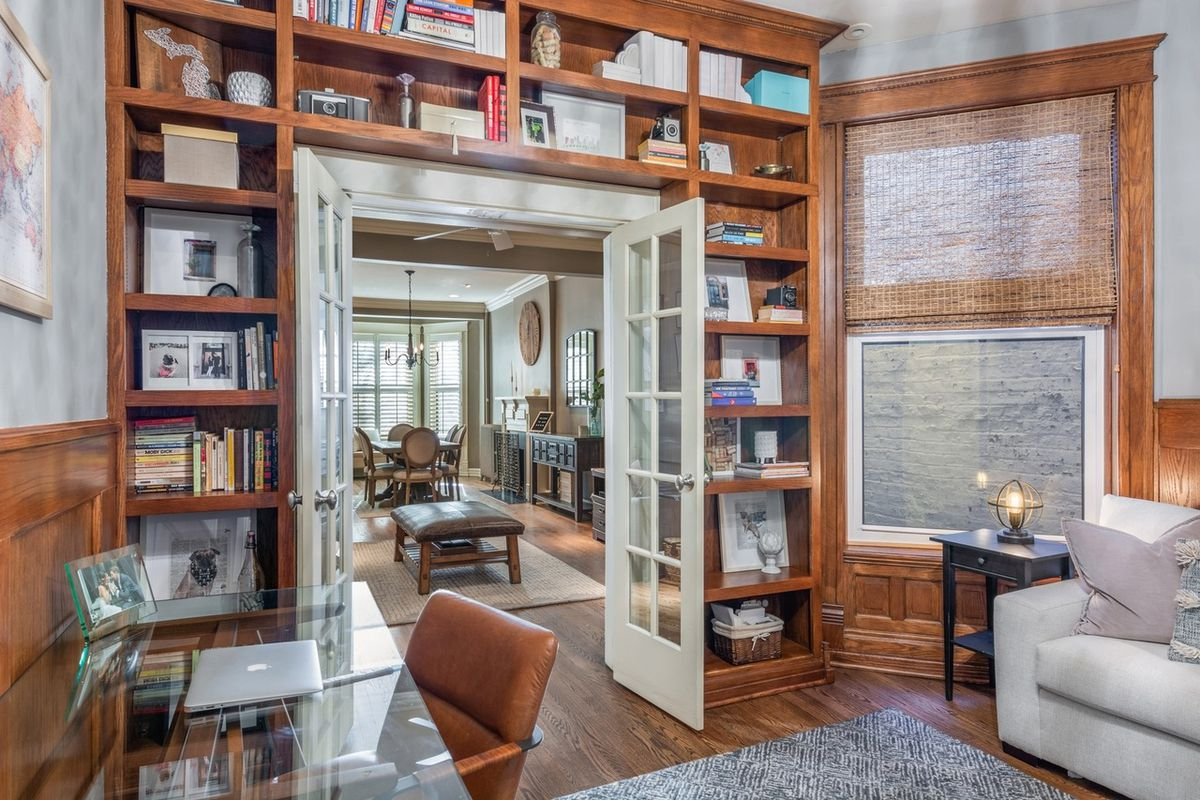 A study with a glass desk, a couch, French doors, and a built-in book shelf.