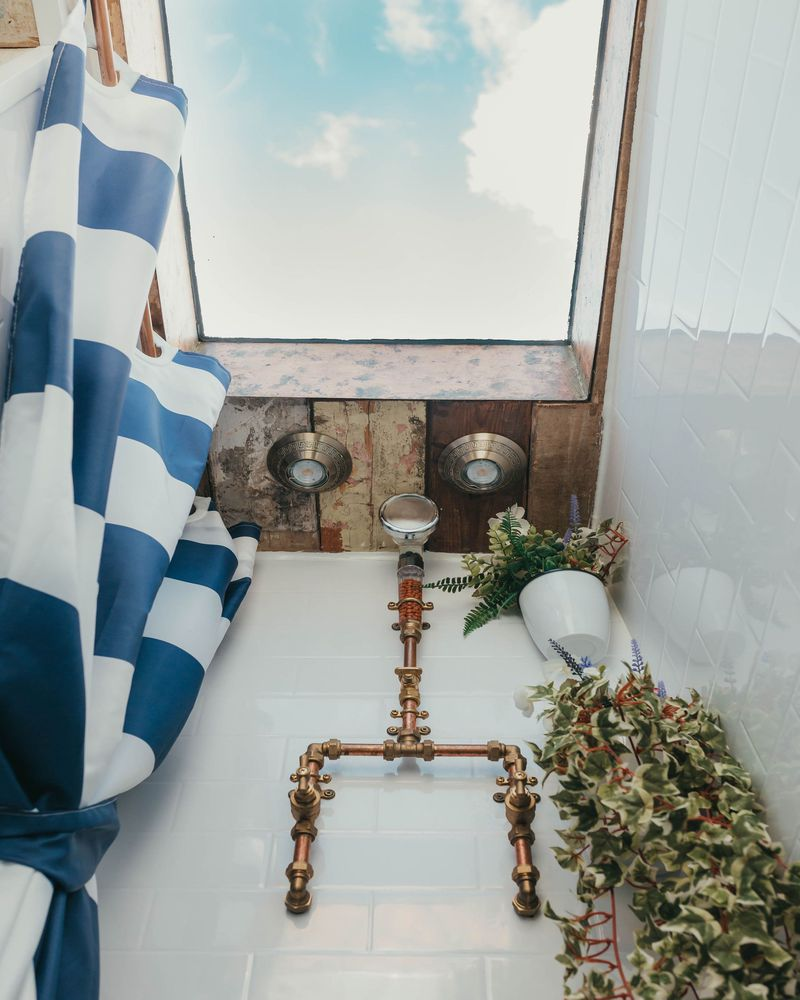 A shower area has white subway tile, a blue and white shower curtain, copper pipes, a skylight, and fake greenery.