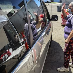 Raymette Francom, a volunteer with the Salt Lake City Mission, waves after putting a box of food into the car during the mission's Father's Day Food Box Giveaway in Salt Lake City on Friday, June 19, 2020. The mission is providing relief to families suffering financial loss due to the COVID-19 pandemic. The volunteers loaded food boxes into cars as they drove up to the mission's Salt Lake location at 1151 South Redwood Road.