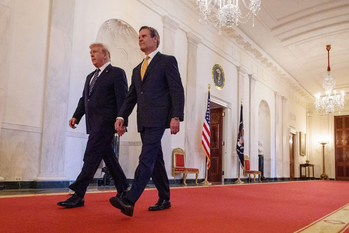 Tennessee Governor Bill Lee walks behind former President Donald Trump on a red carpet within the White House.