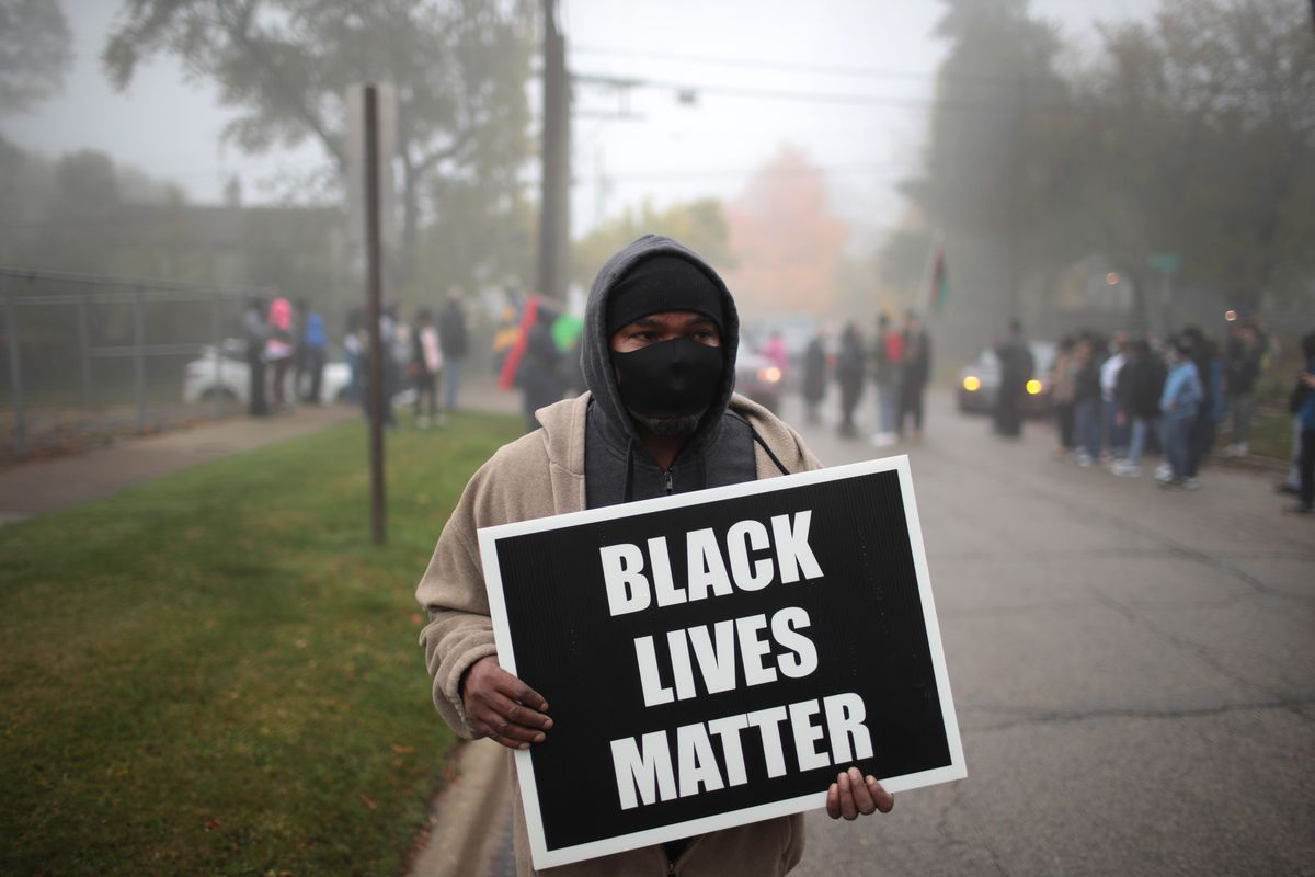 """A middle-aged Black man in a tan coat, black cap and black face mask, holds a black-and-white sign reading """"Black Lives Matter,"""" with other demonstrators behind him in a city street."""