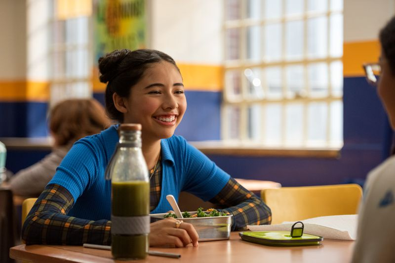 A Latina girl sits at a cafeteria table, smiling, with a salad and a bottle of green juice in front of her.
