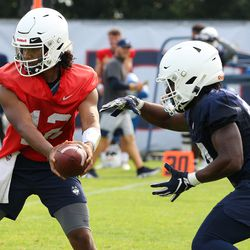 UConn's Tyler Phommachanh #12 hands off to Max Modeste #44 during UConn Huskies football practice on Saturday, August 7, 2021