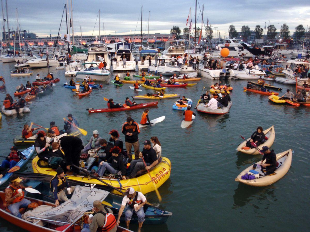 Many people on boats in a boat marina.