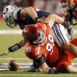 Brigham Young Cougars quarterback Riley Nelson (13) fumbles the ball as Utah Utes defensive end Joe Kruger (99) defends  in Salt Lake City  Sunday, Sept. 16, 2012.