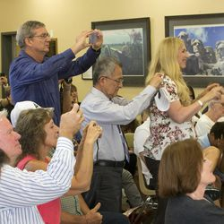 Family members of the graduates take photos as the World Spiritual Health Organization holds their combined board certification and chaplain graduation ceremony at the William E. Christofferson, Salt Lake Veterans Home on Wednesday, Aug. 2, 2017.
