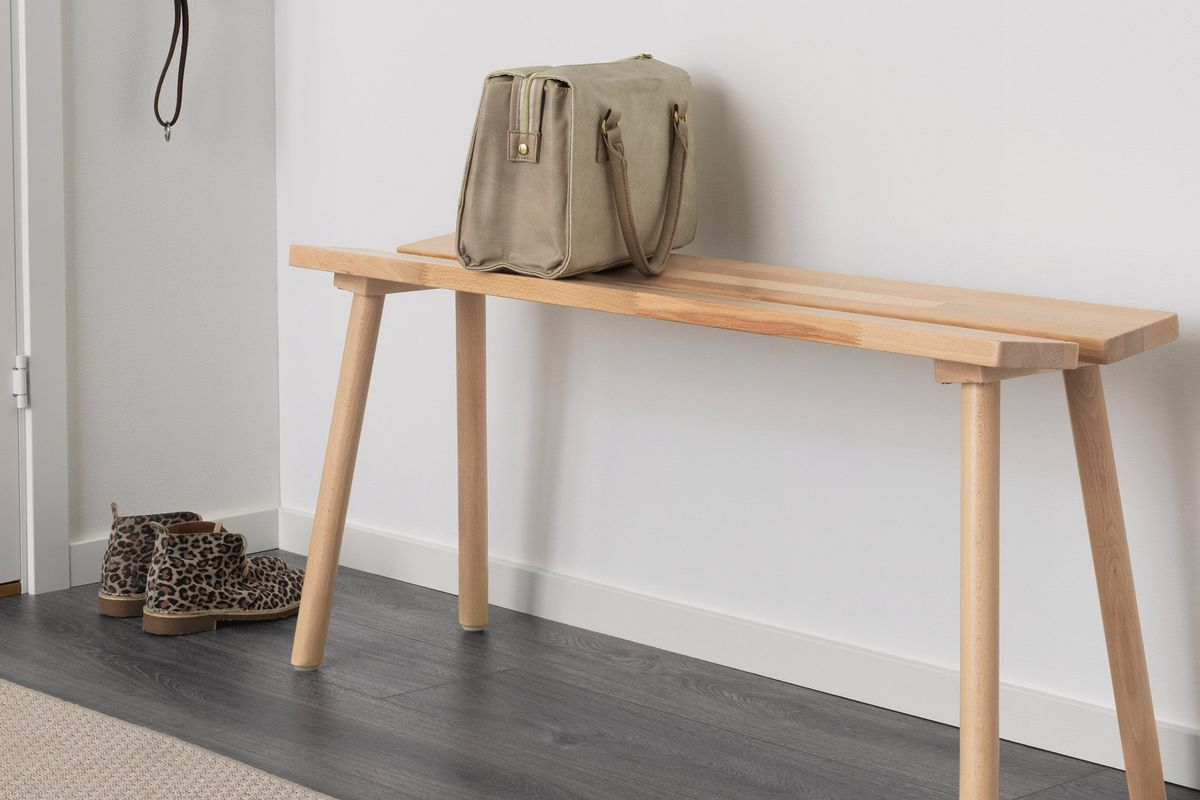 A simple wooden bench with two planks for the seat against a wall set by the door.