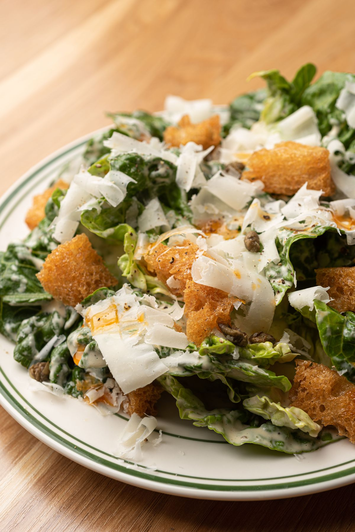 A close up shot of a salad with croutons and shaved cheese.