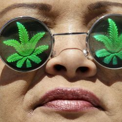 Medical marijuana supporter Lisa Marie Hopwood poses for photographs while wearing marijuana leaf glasses during a rally outside of the Ronald V. Dellums Federal Building in Oakland, Calif., Friday, April 20, 2012.
