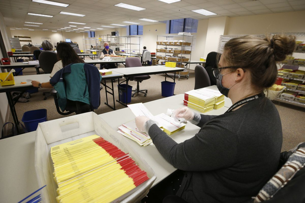 A photo of an election worker opening mail-in ballots.