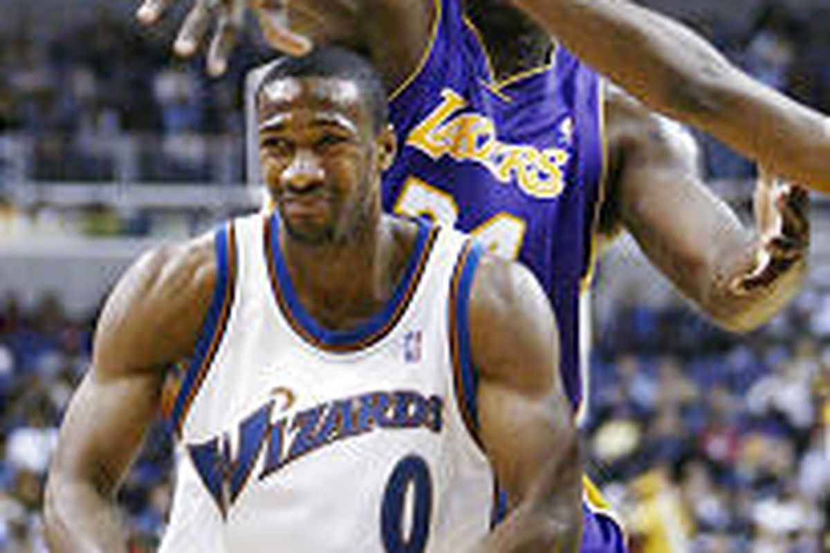 Lakers' Shaquille O'Neal drapes a massive arm across the head of<BR>   Wizards' guard Gilbert Arenas during Saturday's game in Washington.
