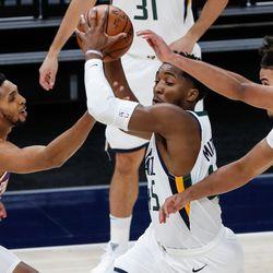 Utah Jazz guard Donovan Mitchell (45) dribbles against Phoenix Suns guard Cameron Payne (15) and forward Cameron Johnson (23) during an NBA preseason game at Vivint Smart Home Arena in Salt Lake City on Saturday, Dec. 12, 2020.