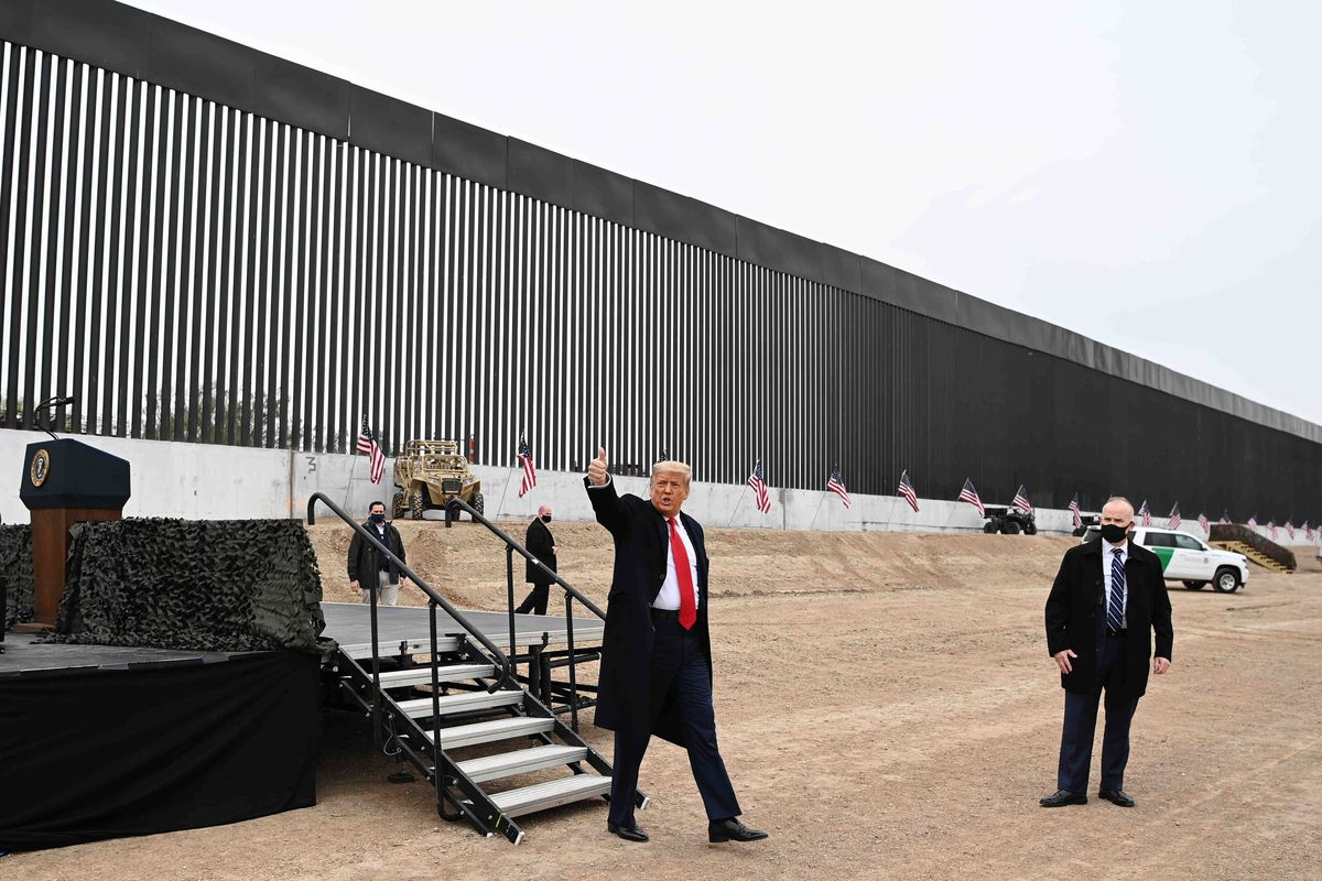 Trump, in a long unbuttoned black dress coat, wind pulling at his bright red tie, smiles and raises his right arm, giving a thumbs up. Behind him loom the massive black bars of the border wall, dark against a grey sky.
