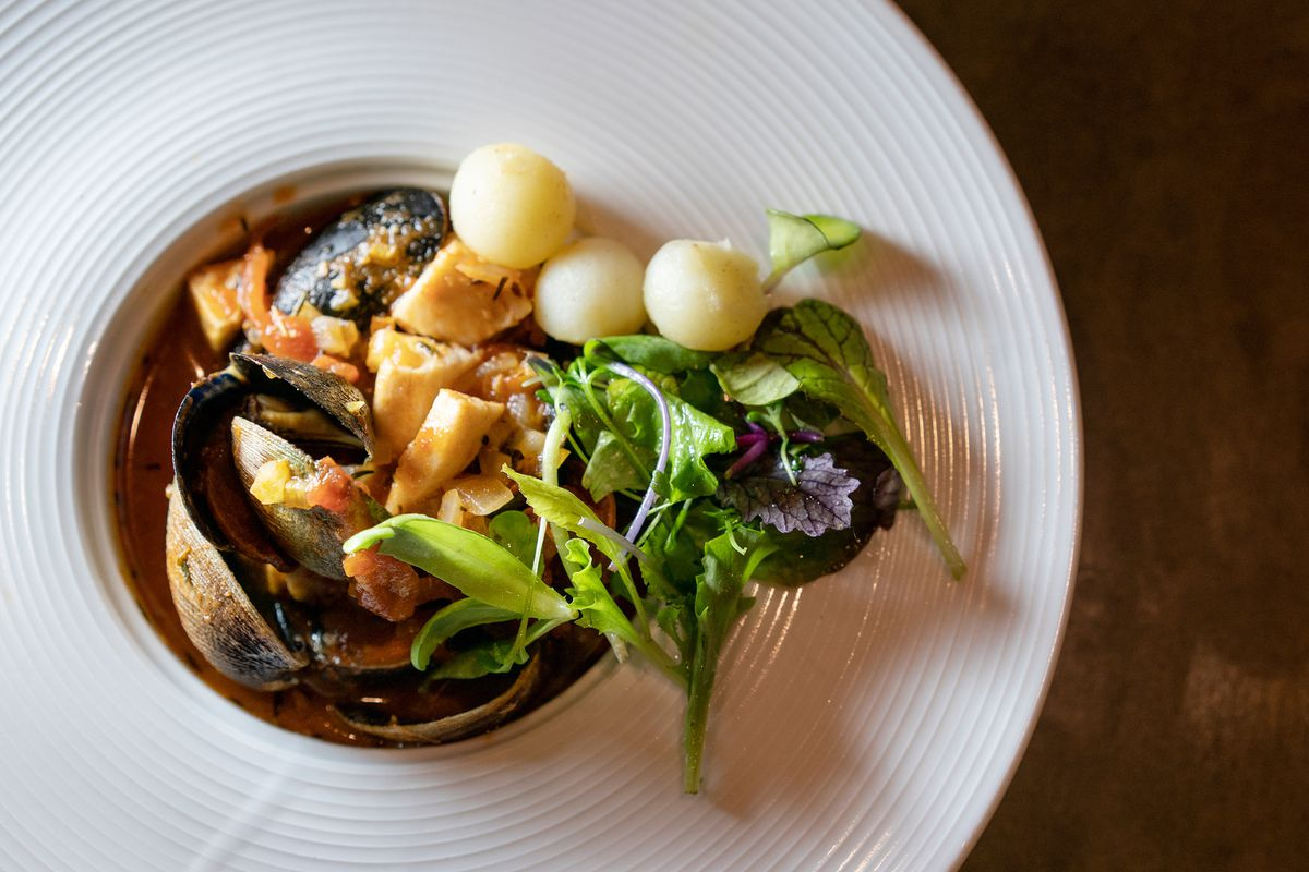 A wide white dish with an indentation in the center holds mussels with tourneyed potatoes and a small herb salad
