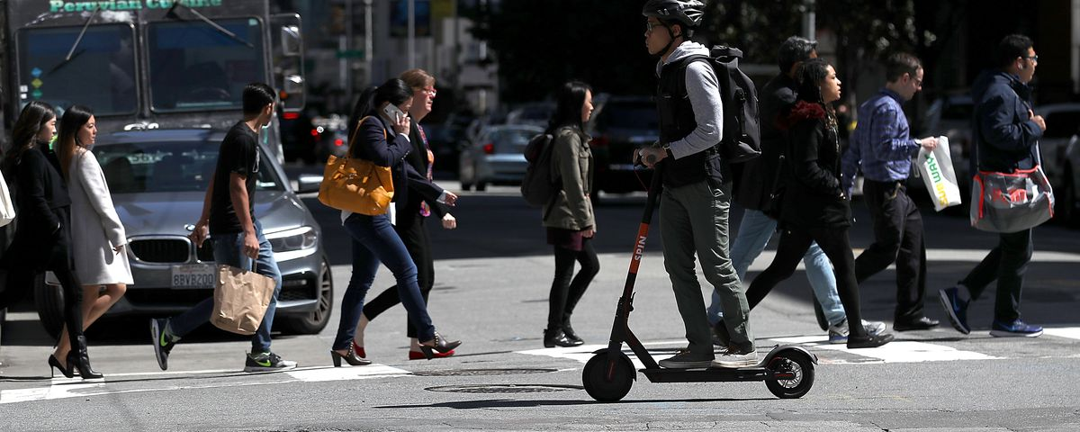A man rides an electric scooter in a crosswalk with pedestrians in downtown San Francisco.