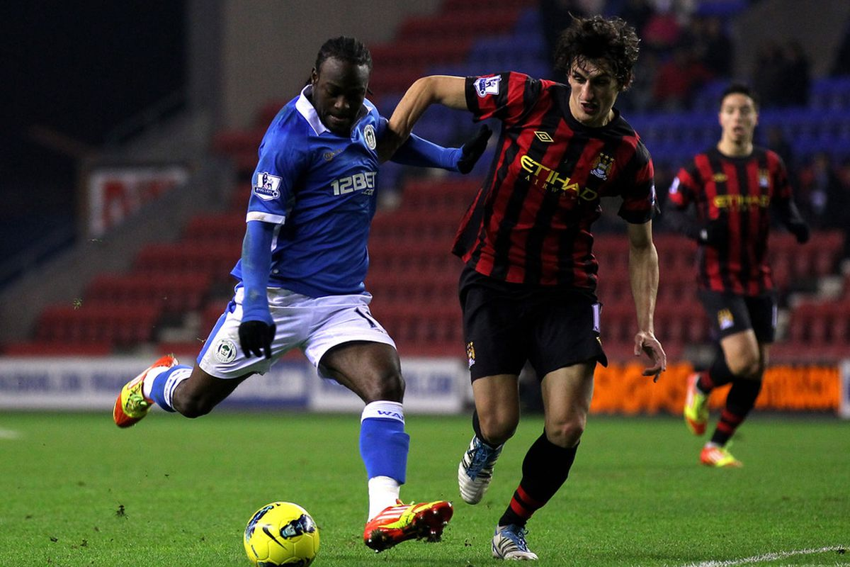 Victor Moses of Wigan Athletic competes with Stefan Savic of Manchester City during the Barclays Premier League match between Wigan Athletic and  Manchester City at the DW Stadium.