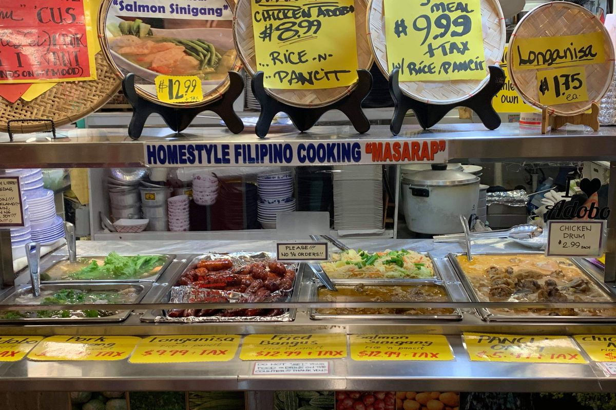 Oriental Mart's counter with food in metal bins displayed and array of colorful signs with different items and prices.