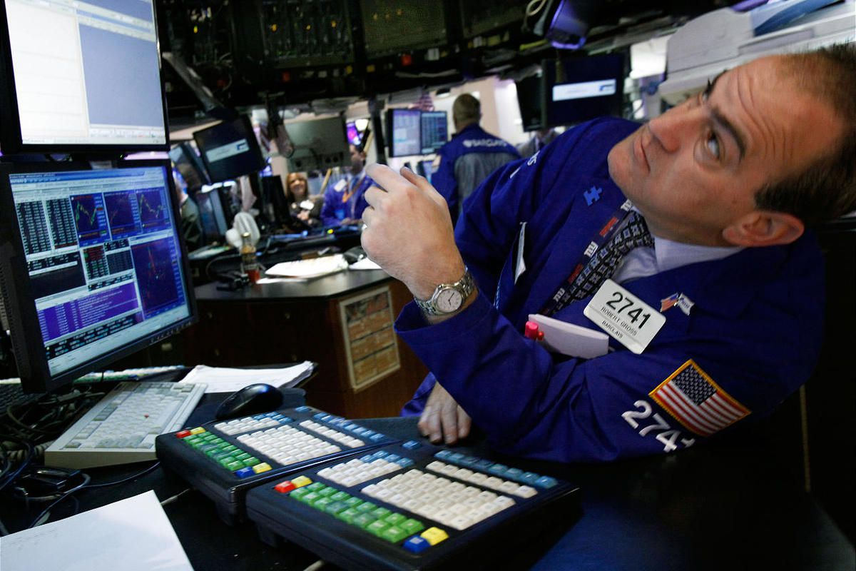 Specialist Robert Gross leans out to check the numbers as he works at his post on the floor of the New York Stock Exchange Monday, April 9, 2012.  The Dow Jones industrial average finished Monday down 130 points at 12,929, its first close below 13,000 sin