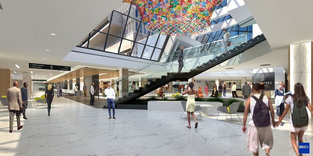 A rendering of the interior of a shopping center (Peachtree Center). There is a glass skylight with colorful lights. There are people walking on the ground floor.