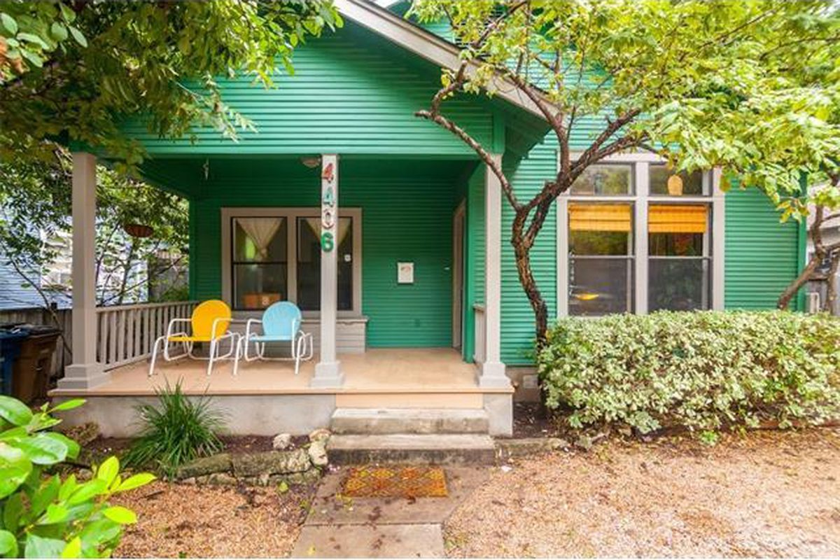 Wooden frame 1925 bungalow with fairly big front porch, painted bright green with colorful porch chairs and a bit of yard in front