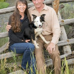 In this July 9, 2015 photo, Karl and Donna Tyler pose for a photo in their ranch with their dog Zip, with the Lemhi River as a back drop, in Leadore, Idaho. The Bonneville Power Administration recently signed a conservation easement with Tyler on about 5,000 acres or ranch land that protects key spawning areas for threatened salmon and steelhead.